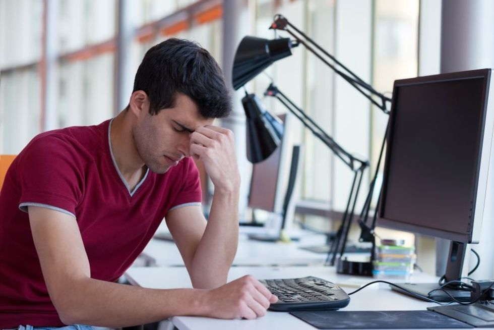 Young worker at desk feeling overwhelmed with his workload.