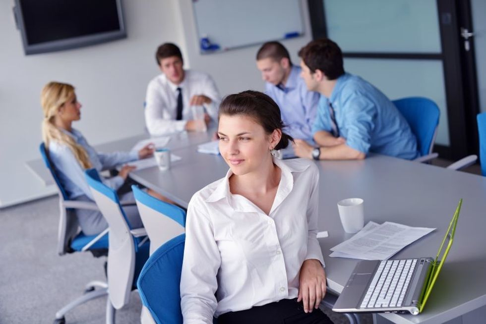 Woman office worker looking lonely and sitting separate from her co-workers at a meeting.