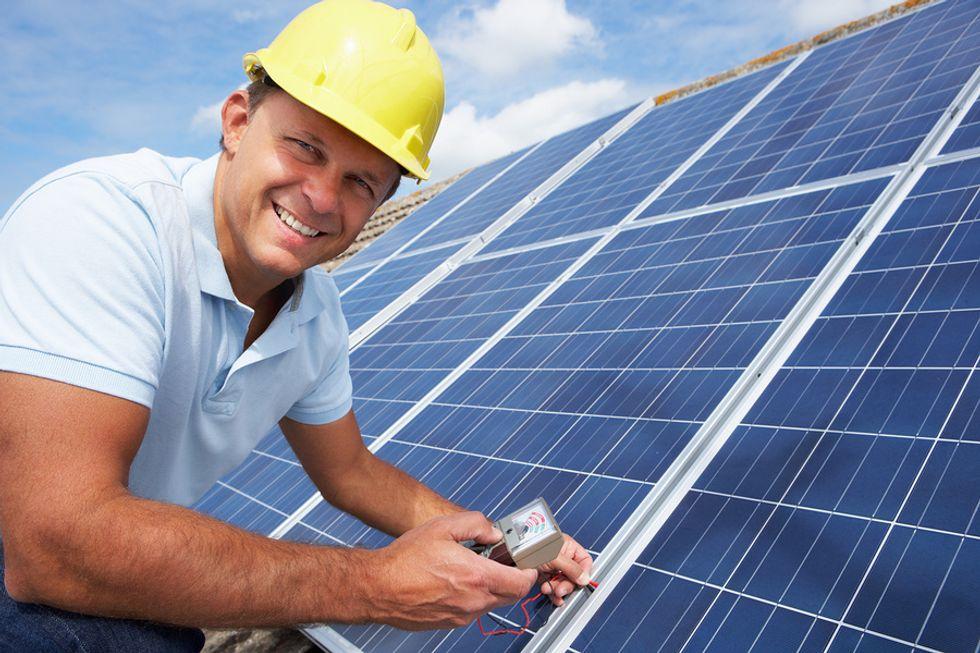 Um instalador solar fotovoltaico que instala painéis solares em um telhado.