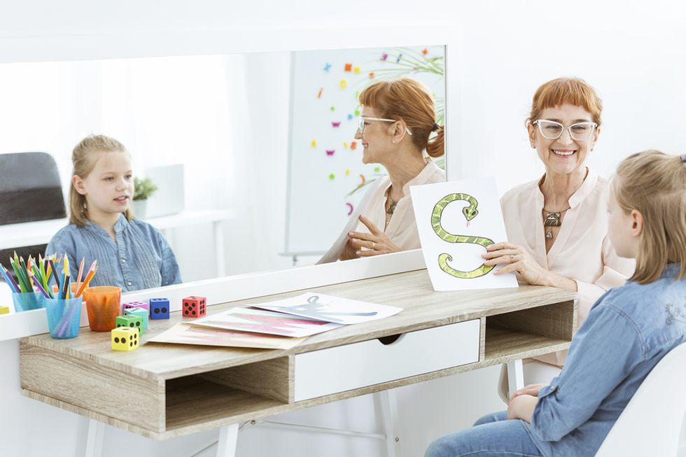 Speech language pathologist working with a young girl in an office.