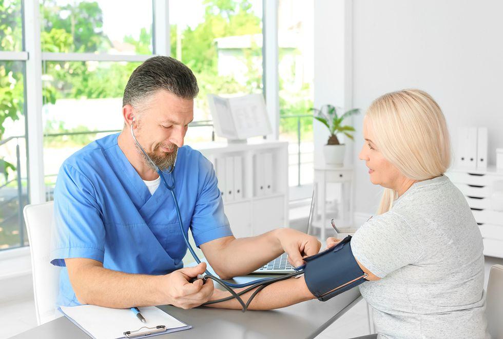Assistente de médico do sexo masculino tomando os sinais vitais de um paciente no consultório médico.