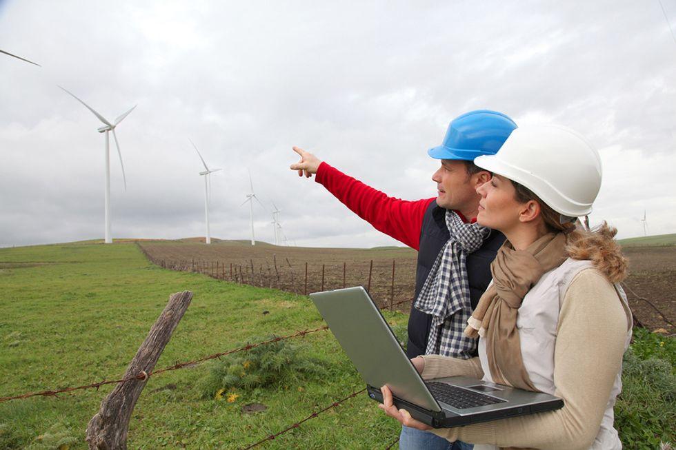 Dois técnicos de serviço de turbinas eólicas pesquisando como consertar uma turbina eólica no exterior.