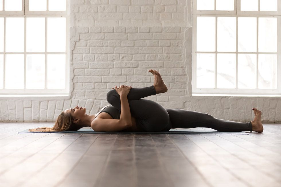 A woman lying on her back on a yoga mat, with one knee pulled into her chest.