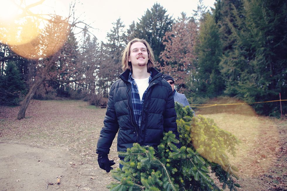Young man works a seasonal job at a Christmas tree farm during the holiday season.