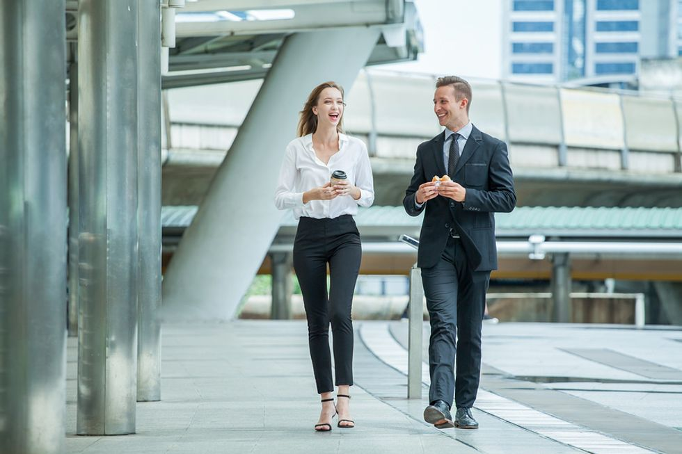 Businessman and businesswoman taking a break from work and walking outside in order to be more productive.