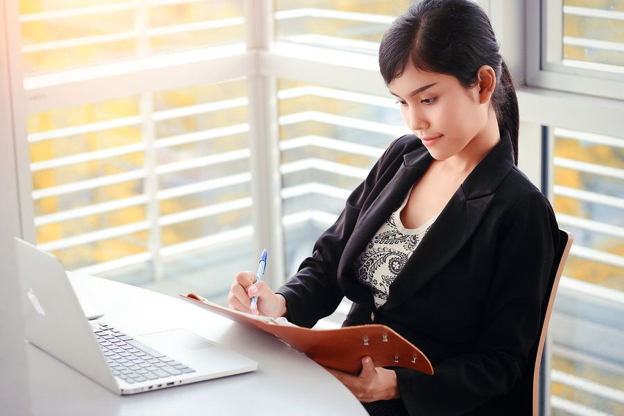 Businesswoman outlining her priorities on a notebook at her desk and making herself more productive at work.