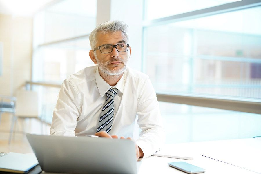 Businessman thinking about what his long-term work goals are in order to be more productive at work.