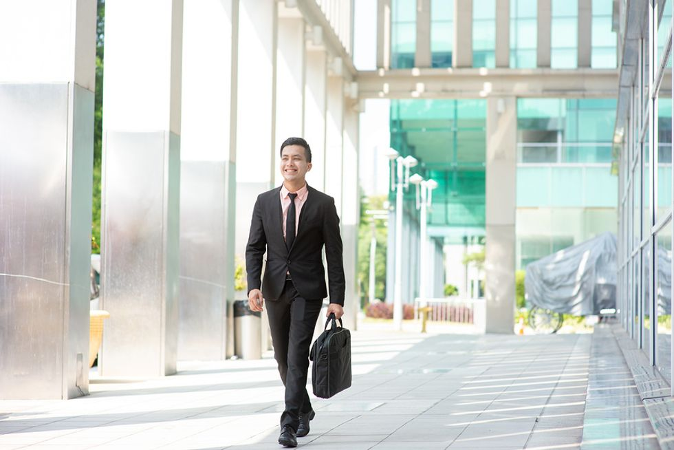 Businessman arriving at his modern office early in order to build better habits and be more productive at work.