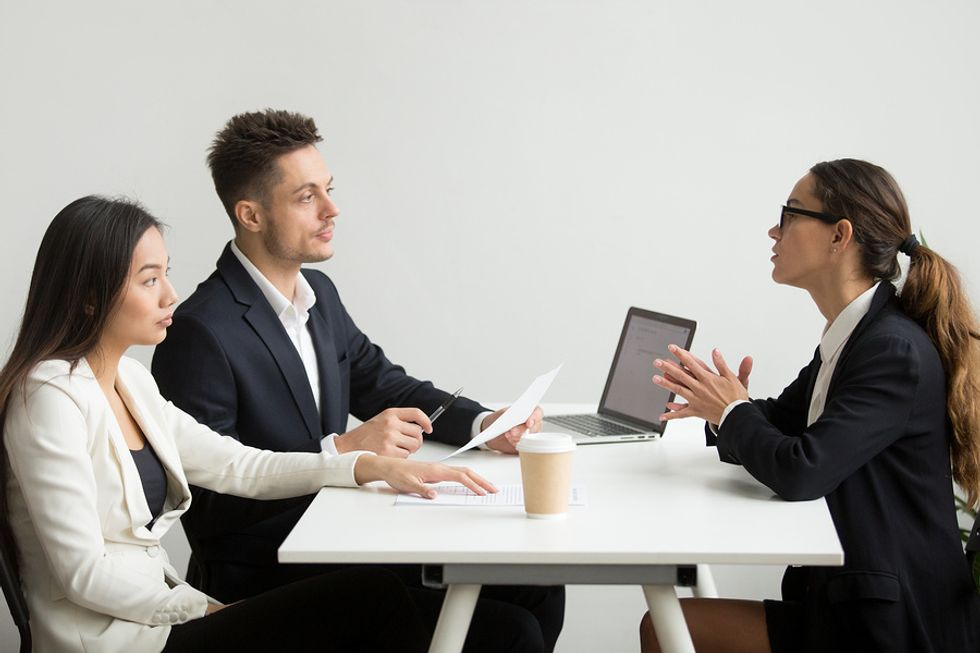 Male and female co-workers discussing how they can work better together in the office with their boss.