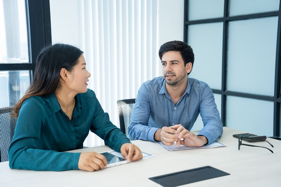 Male and female co-workers sitting next to one another at a desk, sharing why they think their relationship as co-workers is difficult.
