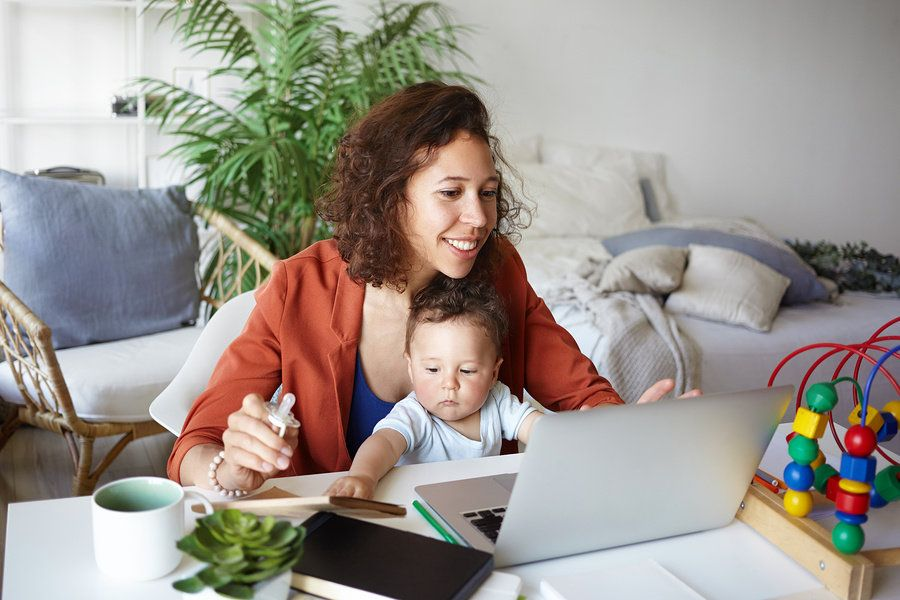 Working mom charting out her daily tasks on the computer while caring for her child.