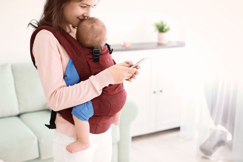 Working mom using her cell phone to look up apps that help her build good professional and personal habits.