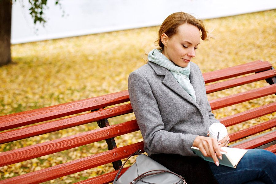 Working mom taking some time to herself, sitting on a bench in the park, drinking coffee and writing in a journal.