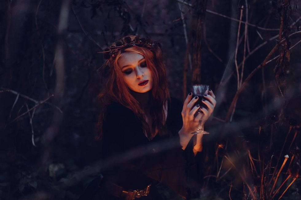 A woman in dark clothing around a gothic scence, holding a glass up with both hands.