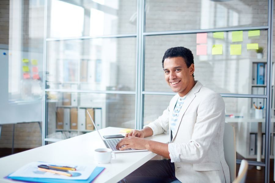 Smiling professional man working on his laptop in his office at his dream job.