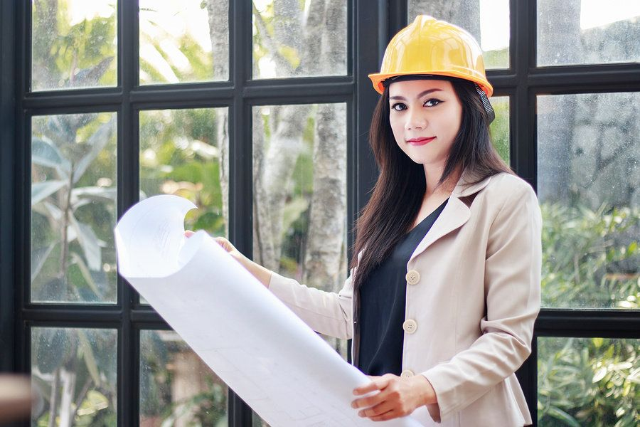 Female civil engineer wearing a hardhat and looking at blueprints while working onsite.