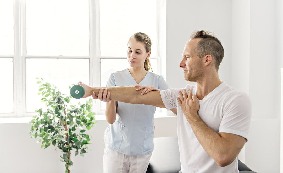 Female physical therapist helping male patient regain movement in his right arm.