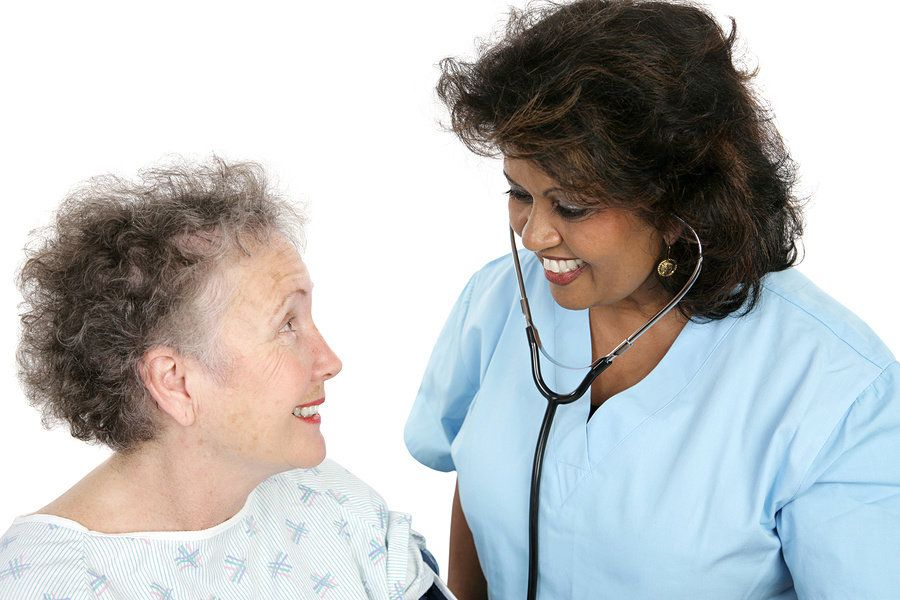 Female nurse practitioner checking up on an elderly female patient in a medical office.