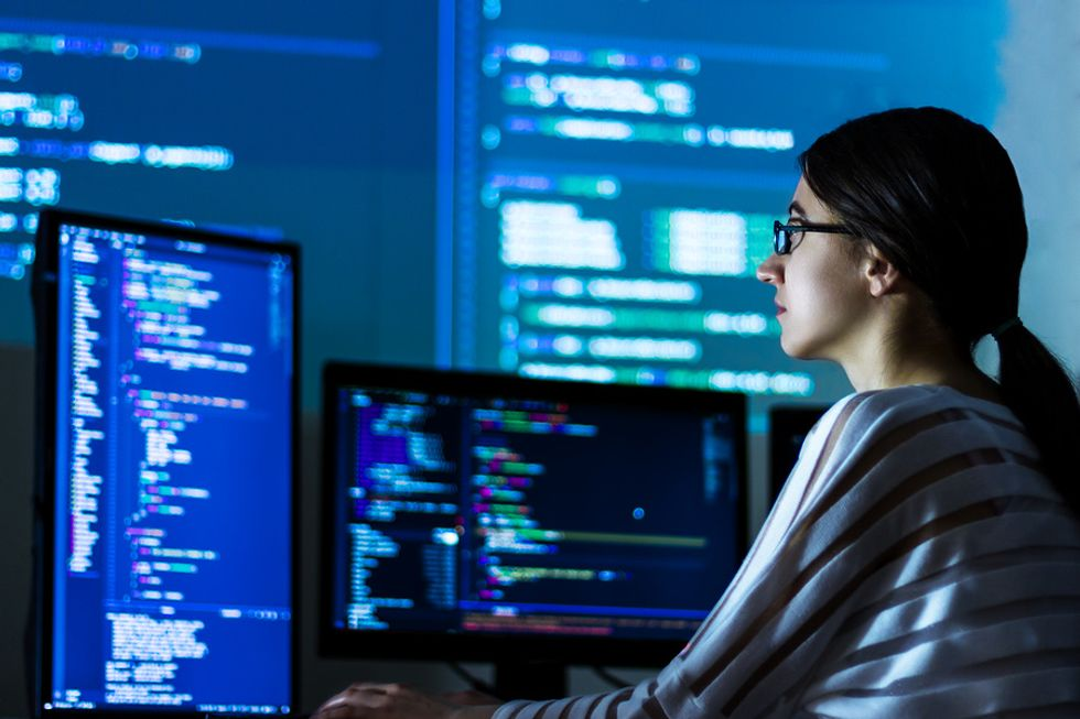 Female software developer coding a new software in her office.