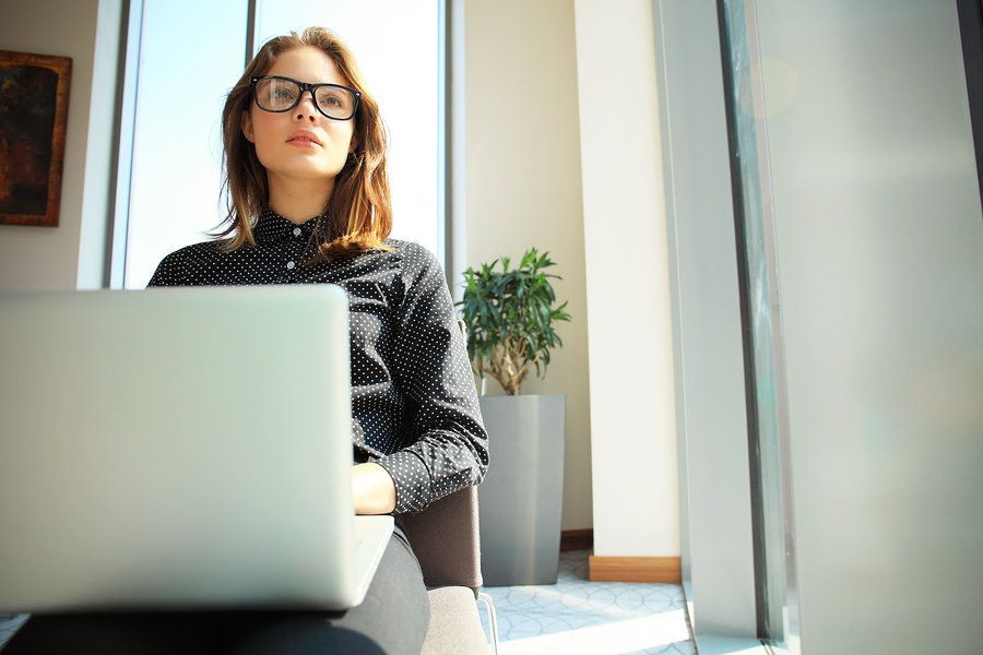 Female operations research analyst working on laptop in office and finding solutions to business issues.