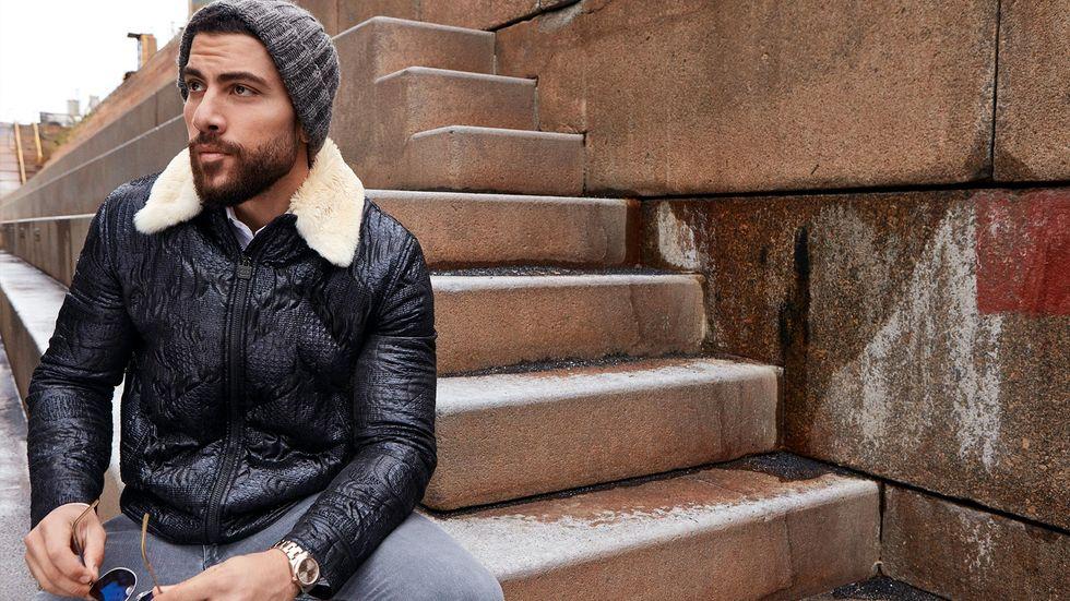 Zeeko Zaki of FBI in a gray wooly hat and black shearling coat sitting on steps