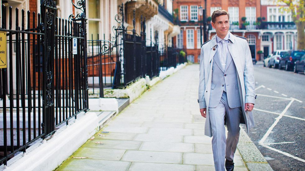 Brian Dietzen in a baby blue suit and overcoat walking through the streets of Kensington in London