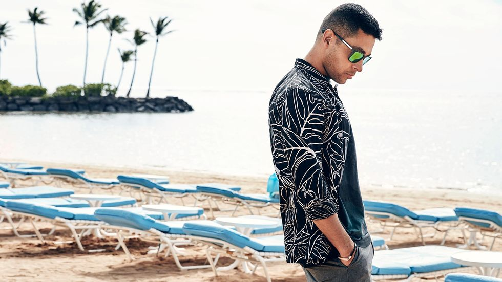 Wilmer Valderrama in a printshirt on a beach in Hawaii.