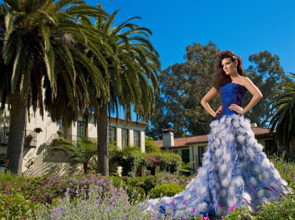 Daniela Ruah of NCIS Los Angeles in blue floral ballgown in flower garden