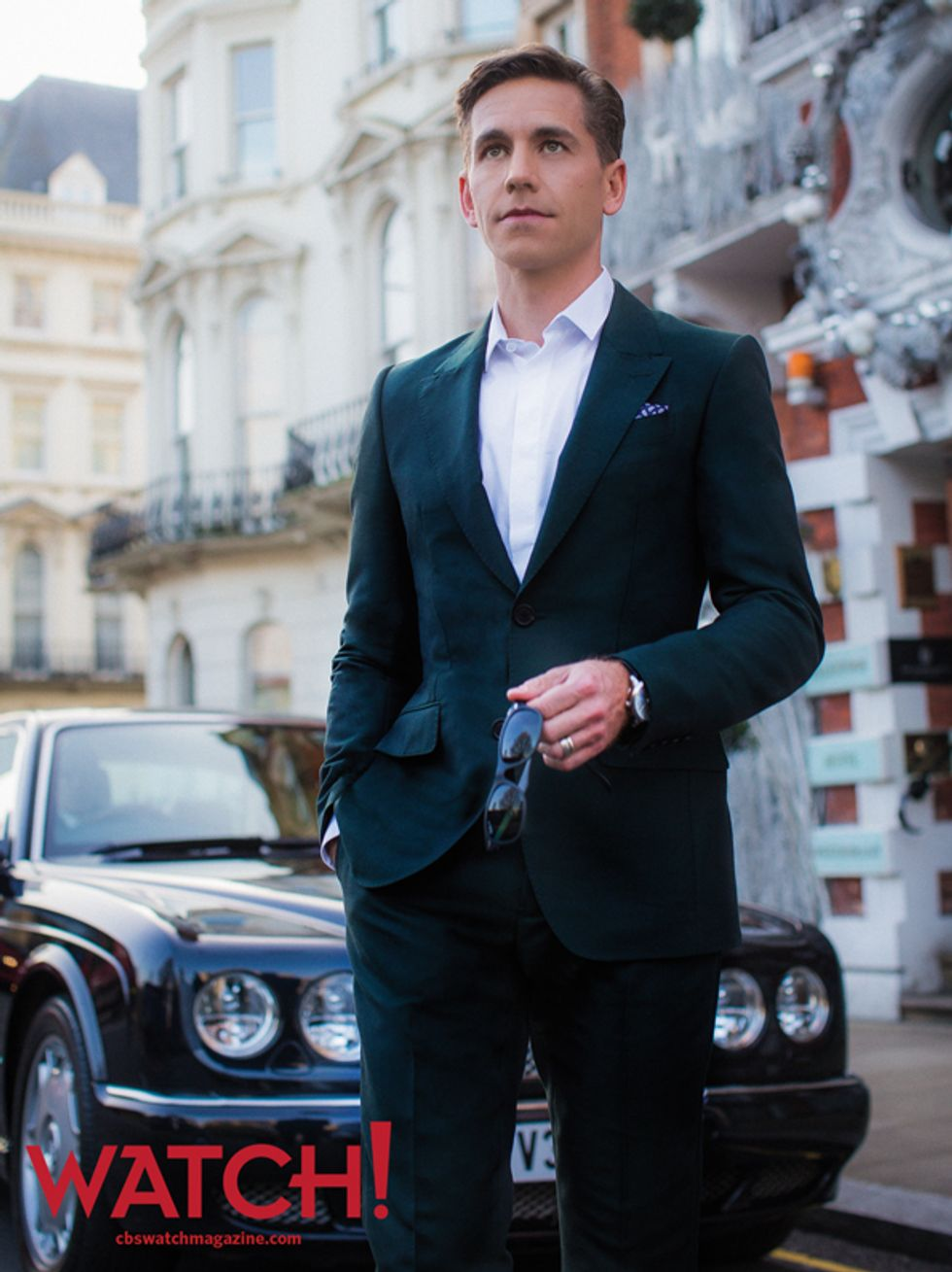 Brian Dietzen holding a pair of sunglasses and wearing a suit while standing in front of a Bentley