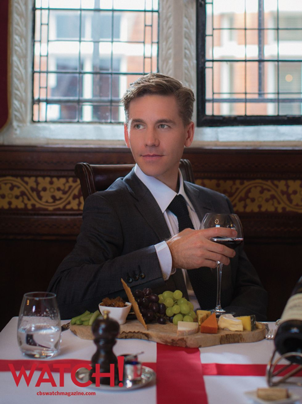 Brian Dietzen having a glass of red wine at a table with a charcuterie board