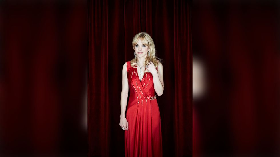 Anna Faris in red dress in front of curtains