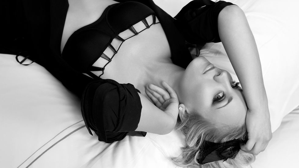 Kaley Cuoco dressed in black on hotel bed