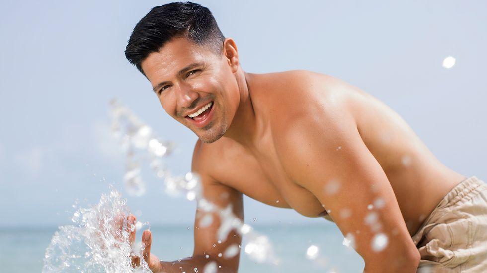 Jay Hernandez of Magnum PI shirtless splashing water