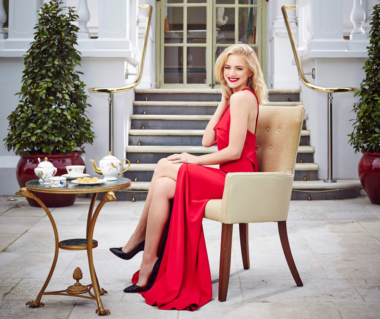 Emily Wickersham suits on a patio wearing an elegant red dress while having tea.
