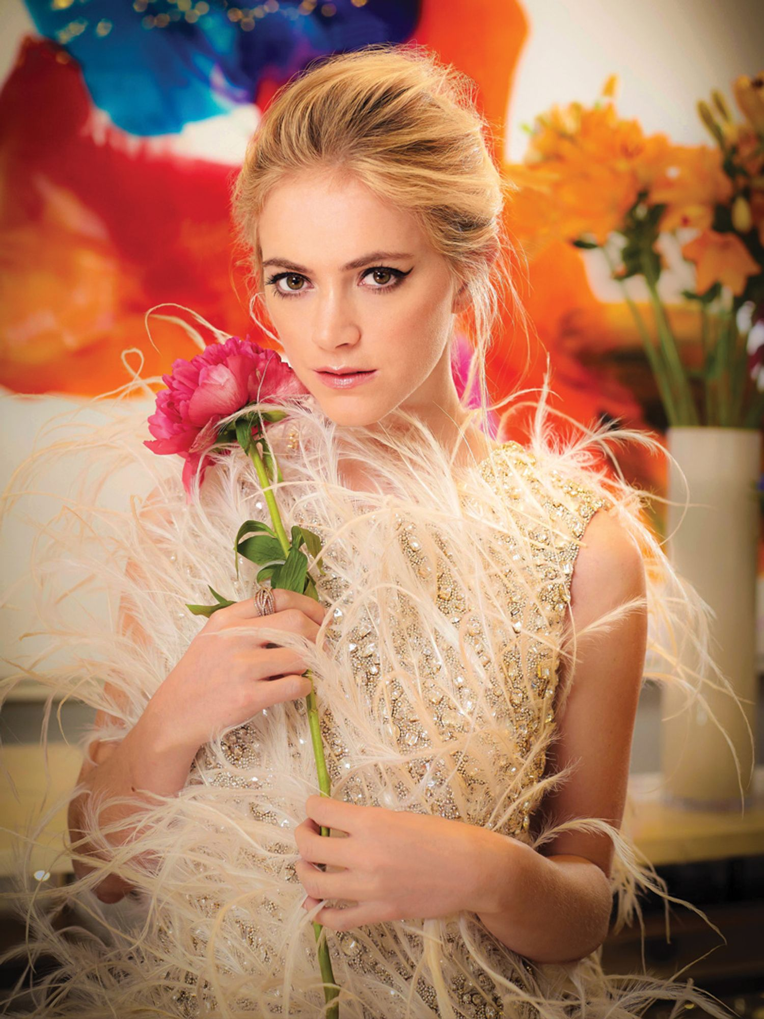 Emily Wickersham in a plumed and sequined dress holding a flower.