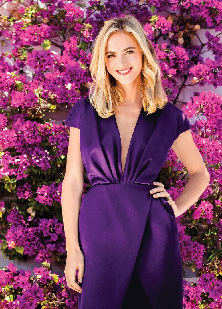 Emily Wickersham wears a purple dress in front of a vibrant flowering bush.