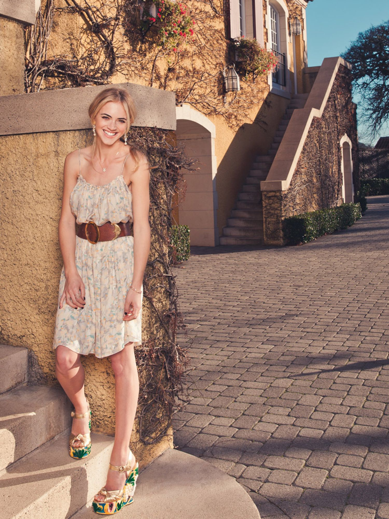 Emily Wickersham wears a belted dress and enormous platform heels.