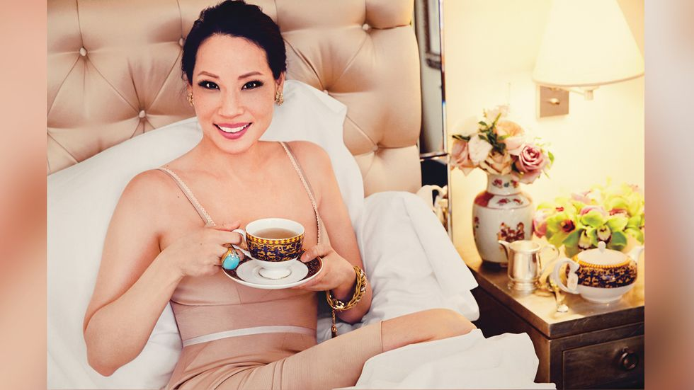 Lucy Liu holding a cup of tea in bed smiling