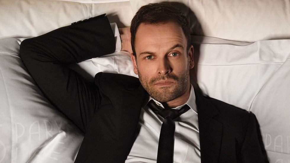 Jonny Lee Miller wearing in suit laying in bed