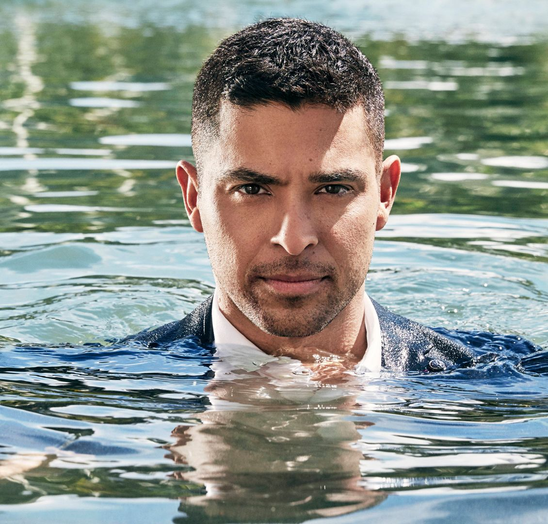 Wilmer Valderrama rises fully dressed from a swimming pool.