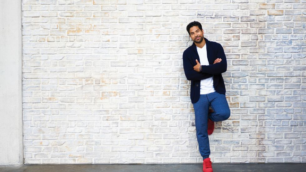 Adam Rodriguez leaning against brick wall wearing blue pants and red shoes