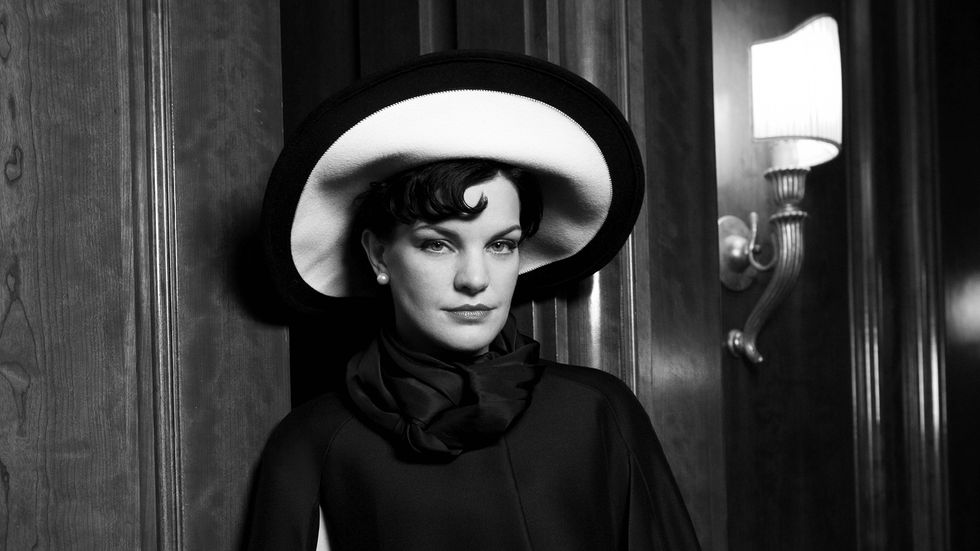 Black and white image of Actress Pauley Perrete wearing a stylish hat.