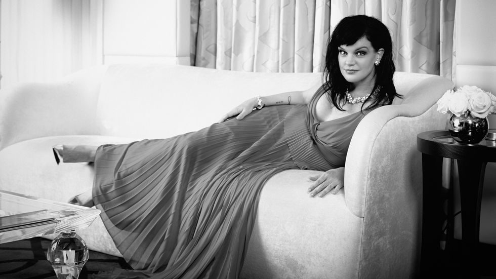 Black and white image of Actress Pauley Perrete reclining on a couch in a pleated dress.