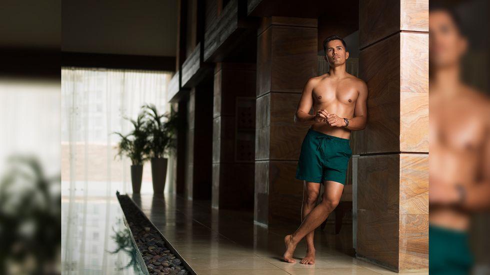 Jay Hernandez in green swim trunks by an indoor pool