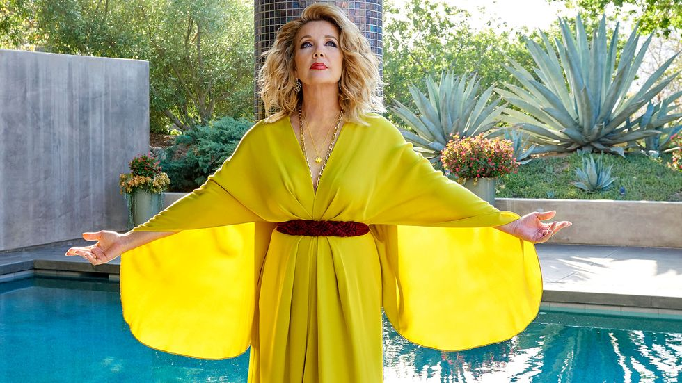 Melody Thomas Scott stand poolside with her arms outstretched wearing a flowing yellow dress.