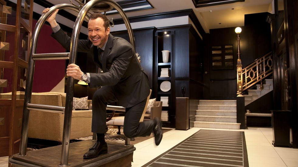 Donnie Wahlberg having fun in on hotel luggage cart