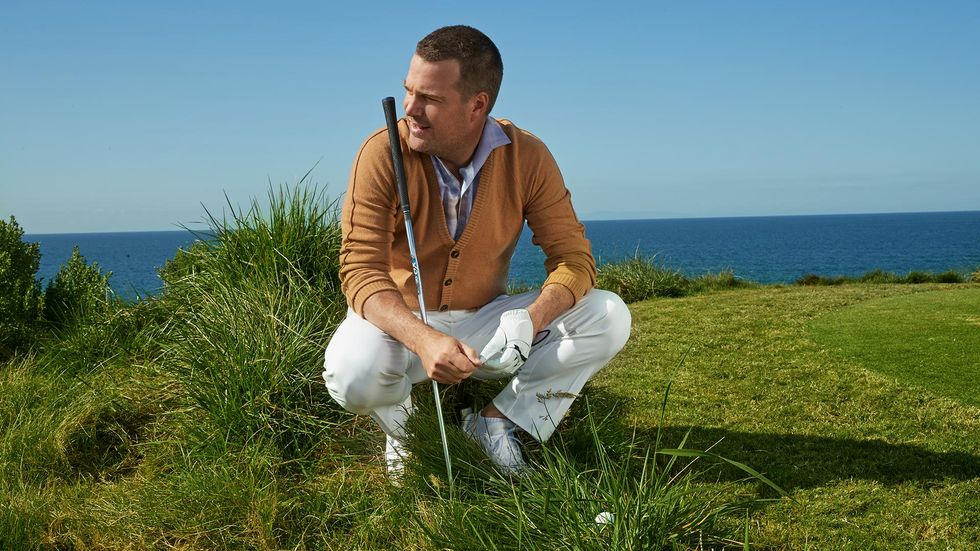 Chris O'Donnell squatting in the grass with a gold club sitting on his shoulder