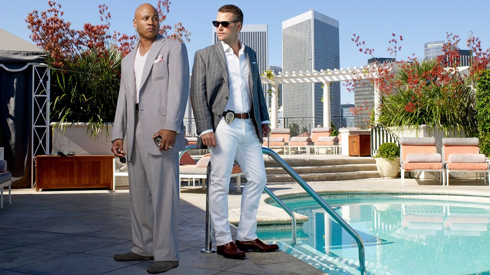 LL COOL J and Chris O'Donnell in suits and holding their badges by a pool