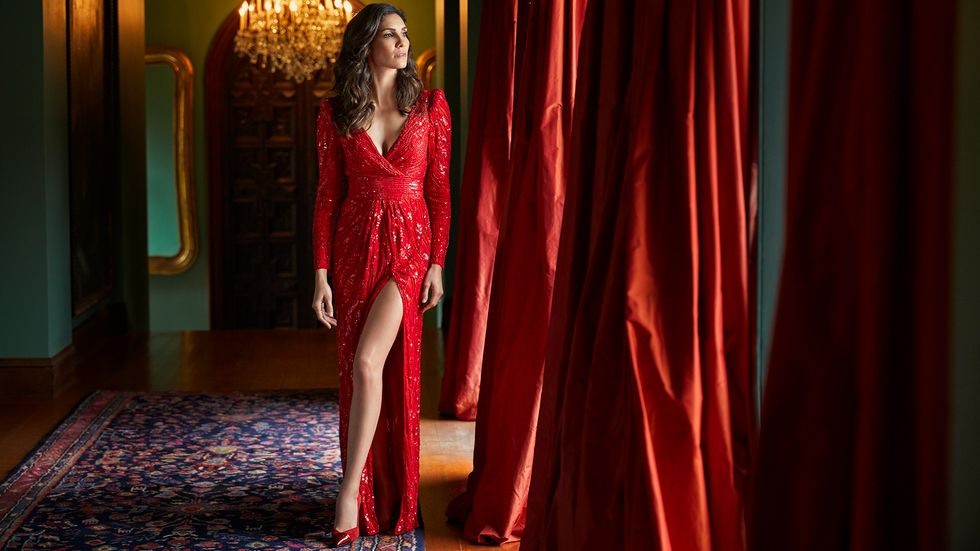 Daniela Ruah in a rich red dress with a high slit on her leg in a room with matching red draperies