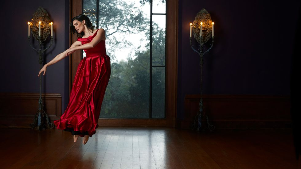 Daniela Ruah in a rich red dress leaping delicately into the air